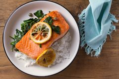 Salmon fillet with rice, spinach and lemon. Salmon with garnish. Fish for healthy dinner. View from above, top Royalty Free Stock Photos