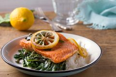 Salmon fillet with rice, spinach and lemon. Salmon with garnish. Fish for healthy dinner. Salmon fillet with rice, spinach and lemon. Salmon with garnish. Fish Stock Photos