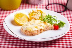 Salmon fillet served with risotto, arugula salad and lemon on white plate. Close up royalty free stock photography