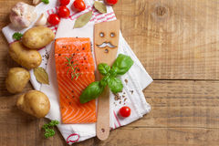 Salmon fillet with spatula, spices and vegetables Royalty Free Stock Image