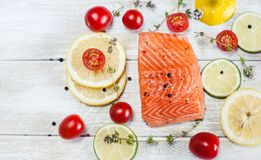 Salmon Fillet On A Table. Fresh raw salmon fillet on wooden rustic table - top view. Healthy food, diet or cooking concept Stock Photos