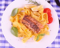 Salmon fillet on tagliatelle, herbs, lemon Royalty Free Stock Photography