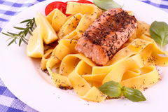 Salmon fillet on tagliatelle, lemon and herbs Royalty Free Stock Photography