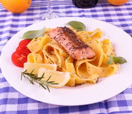 Salmon fillet on tagliatelle, lemon, herbs Stock Photos
