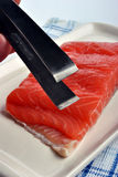 Salmon fillet and a tongs Royalty Free Stock Photos