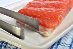 Salmon fillet and a tongs Royalty Free Stock Photography