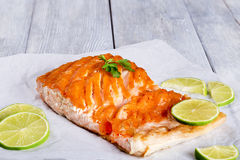 Salmon fillet on a white parchment paper, close-up. Delicious red fish salmon steak fillet on a white parchment paper with sliced lime and parsley on a wooden Royalty Free Stock Photography