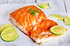 Salmon fillet on a white parchment paper, close-up. Delicious red fish salmon steak fillet on a white parchment paper on a wooden table,  studio lights, close-up Stock Photos
