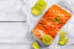Salmon fillet on a white parchment paper, top view. Delicious red fish salmon steak fillet on a white parchment paper with lime slices on a wooden table, blank Royalty Free Stock Images
