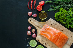 Salmon fillet on wooden board with garnish ready to cook Royalty Free Stock Images