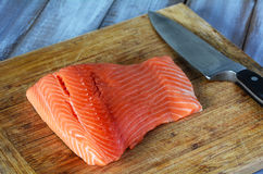 Salmon fillet on wooden board with a knife Stock Photo