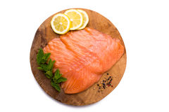 Salmon fillet on wooden board. Salmon fillet with lemon, pepper and mint on wooden board, isolated on white background Royalty Free Stock Images