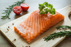 Salmon fillet on wooden board with tomato rosemary and parsley Stock Photos