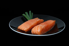 Salmon fillets. Two pieces of raw salmon fillet on a black plate on a black background Royalty Free Stock Image