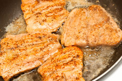 Salmon fillets fried in a pan Stock Photos