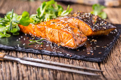 Salmon fillets. Grilled salmon, sesame seeds herb decorationon on vintage pan or black slate board. Fish roasted on an old wooden table.Studio shot stock photo