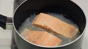Salmon Fillets Poaching. Two wild sockeye salmon fillets poaching in some boiling water in a pan on a gas stove top stock video