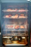 Salmon fillets smoking in a smoker. Fillets of salmon actively smoking in a meat smoker. Plumes of smoke visible stock photography