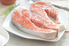 Salmon fillets on a white wooden table next to some salt during food preparation. Cutlery and other cooking utensils Stock Image