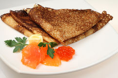Salmon fish and caviar with russian pancakes Stock Photos