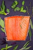 Salmon fish fillet, lemon, lime and herbs: basil, sage, mint, spinach, cilantro, thyme and rosemary like ingredients for cooking Stock Image