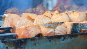 Salmon fish on fire. Salmon fish is  cooking on a grill Royalty Free Stock Photos