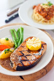 Salmon Fish. Grilled salmon fish served with lemon on top, potatoes, carrots, beans and homemade pineapple sauce Stock Photos