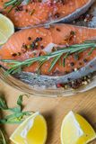 Salmon fish on a plate with spices, olive oil and lemon before cooking, flat lay stock photos