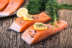 Salmon Fish..Raw salmon fillet pepper salt dill lemon rosemary on wooden table Royalty Free Stock Photography