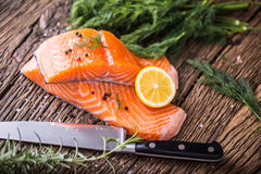 Salmon Fish..Raw salmon fillet pepper salt dill lemon rosemary on wooden table Royalty Free Stock Image