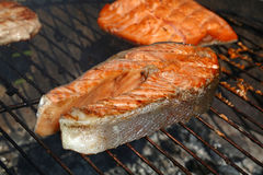 Salmon fish steak barbecue grill cooking close up. Grilled salmon fish steak barbecue meal cooking, prepared on bbq grill, close up stock photos