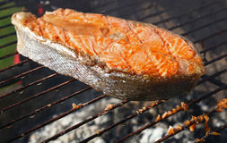 Salmon fish steak barbecue grill cooking close up. One grilled salmon fish steak barbecue meal cooking, prepared on bbq grill, close up royalty free stock photos