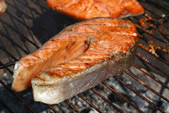 Salmon fish steak barbecue grill cooking close up. One grilled salmon fish steak barbecue meal cooking, prepared on bbq grill, close up stock image