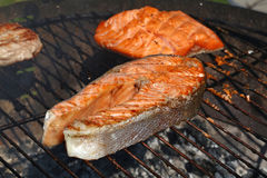 Salmon fish steak barbecue grill cooking close up. One grilled salmon fish steak barbecue meal cooking, prepared on bbq grill, close up royalty free stock photo
