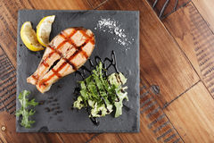 Salmon fish steak with lemon. And greens on a shale surface. wooden background Stock Photography