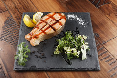 Salmon fish steak with lemon. And greens on a shale surface. wooden background Royalty Free Stock Images