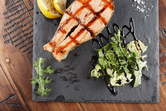 Salmon fish steak. With lemon and greens on a shale surface. wooden background Royalty Free Stock Photo