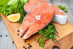 Salmon fish steaks. Raw salmon fish steaks with fresh herbs on cutting board Stock Images