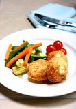Salmon fishcakes served with vegetables and cherry tomatoes. Three salmon fishcakes served with side vegetables Royalty Free Stock Photos