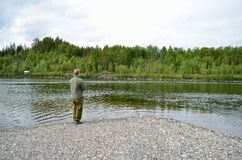 Salmon fisherman reeling in the line. In fresh water river Royalty Free Stock Photos