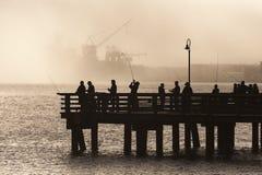 Salmon Fishermen on Elliott Bay in Seattle, Washington. On an early foggy morning on a pier in West Seattle, fishermen jig for salmon with the Port of Seattle stock photo