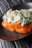 Salmon Florentine is made with juicy, tender, baked salmon and topped with creamy spinach and mushrooms close up on the plate. Salmon Florentine is made with stock photo