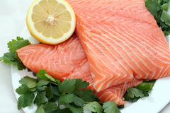 Salmon food. Two pieces of fresh salmon served on a plate with lemon royalty free stock photography