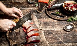 Salmon food. Raw fish. Cutting fresh salmon women's hands. On the old wooden table Stock Image