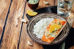 Salmon with Garlic Lemon Butter Sauce and rice. On a wood background. toning. selective focus Stock Photos