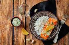 Salmon with Garlic Lemon Butter Sauce and rice. On a wood background. toning. selective focus Stock Photo