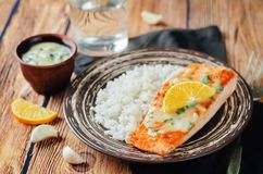 Salmon with Garlic Lemon Butter Sauce and rice. On a wood background. toning. selective focus Stock Photography