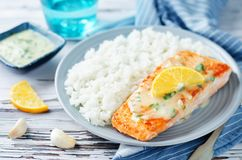 Salmon with Garlic Lemon Butter Sauce and rice. On a wood background. toning. selective focus Royalty Free Stock Image