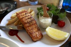 SALMON GRILL WITH cream sauce and french fries. royalty free stock photo