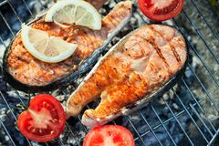 Salmon on grill. Salmon preparation process on wooden grill. Grilled fish steaks on fire. Top view royalty free stock images